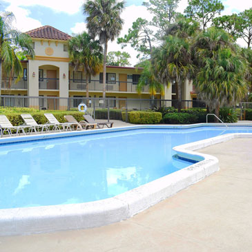 Behavioral health of the palm beaches treatment center pool and patio area with chairs and palm trees
