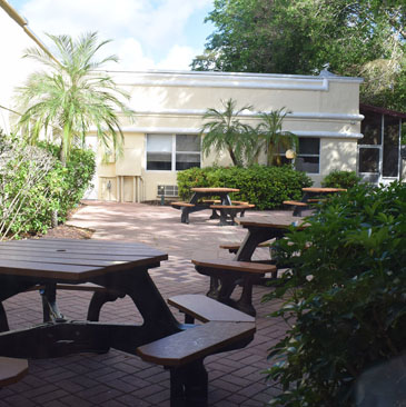 Banyan Boca outdoor waiting area behind yellow building with brown tables and palm trees