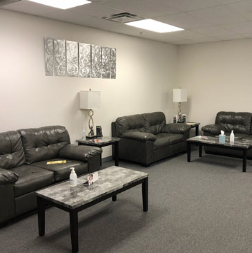 Banyan Massachusetts treatment center waiting area with grey couches and tables