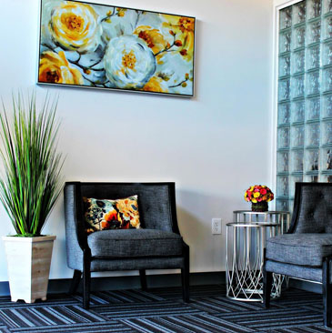 Banyan Philadelphia treatment center waiting area with grey chairs, flower painting, and striped rug